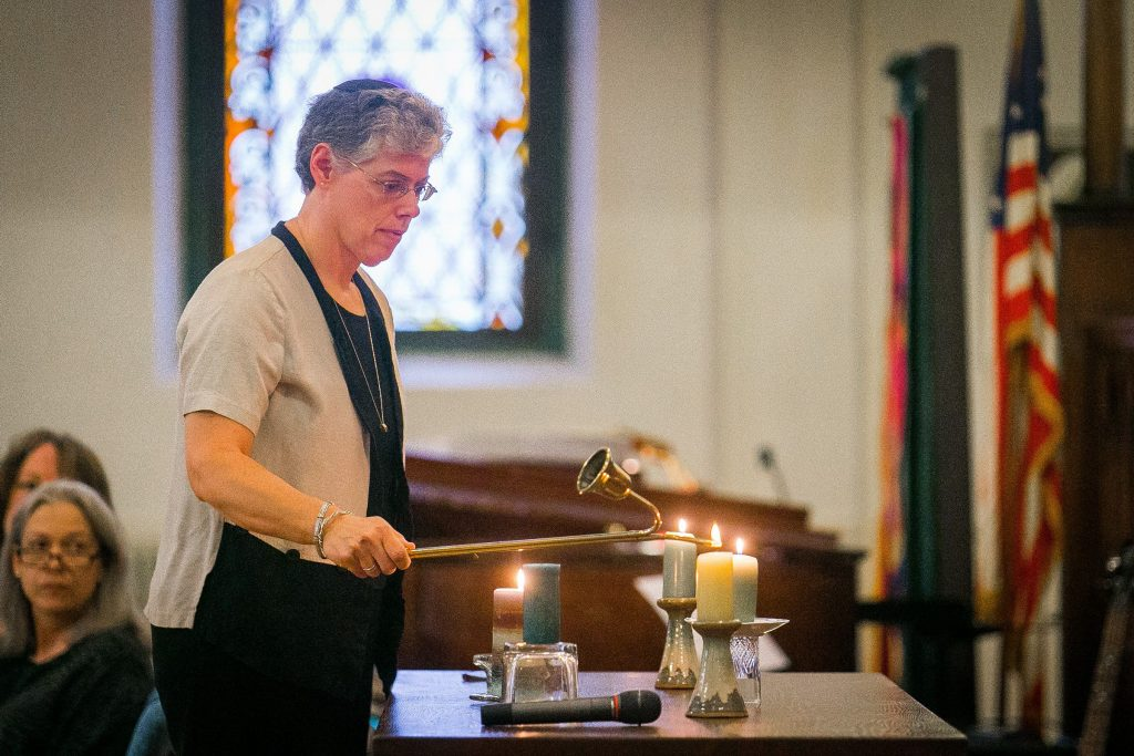 Rabbi Robin Nafshi lights a candle in memory of the victims of last week's mass shooting at Emanuel AME Church in Charleston, S.C., during an interfaith vigil for peace and racial healing at South Congregational Church in Concord, Wednesday, June 24, 2015. Four additional candles were lit in memory of all victims of racial, ethnic, religious violence or hate crimes of any kind.  (ELIZABETH FRANTZ / Monitor staff) Rabbi Robin Nafshi lights a candle in memory of the victims of last week's shooting at the interfaith vigil. in Charleston, S.C., during an interfaith vigil for peace and racial healing at South Congregational Church in Concord, Wednesday, June 24, 2015. Four additional candles were lit in memory of all victims of racial, ethnic, religious violence or hate crimes of any kind.(ELIZABETH FRANTZ / Monitor staff)   ELIZABETH FRANTZ