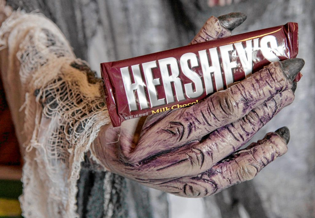 FILE-    This Oct. 21, 2009 file photo shows a Hershey chocolate bar in the hand of a Halloween creature at a display inside Chagrin Hardware in Chagrin Falls, Ohio.  Experts say kids love the gimmicks at Halloween, but the classics, like this Hershey bar, remain strong sellers.   (AP Photo/Amy Sancetta, FILE) Amy Sancetta