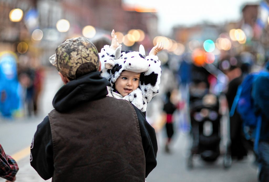 Lumin Perron, 2, in her cow costume walks down Main Street in Concord with her dad Taylor during the Halloween Howl on Friday evening, October 25, 2019. GEOFF FORESTER