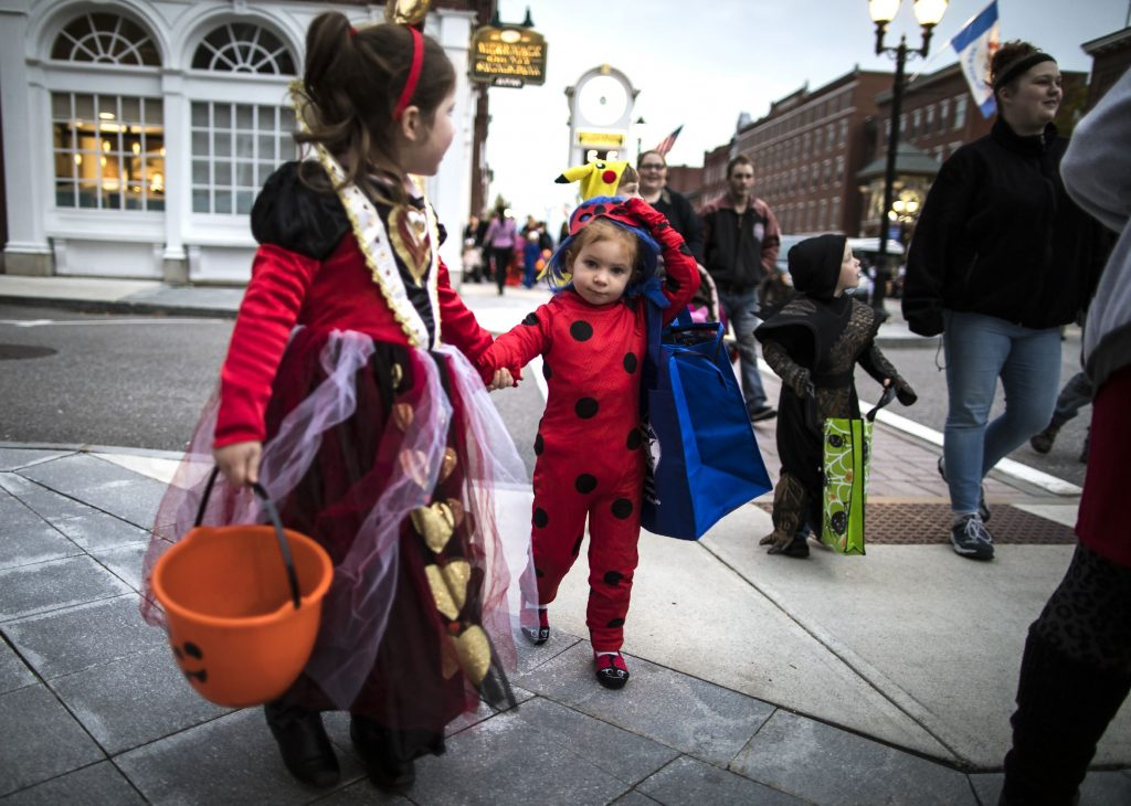 Morgan Hallee, 5, (left) and her cousin Aubree Cate, 3, of Manchester make their way down Main Street at the Halloween Howl on Friday evening, October 25, 2019. GEOFF FORESTER