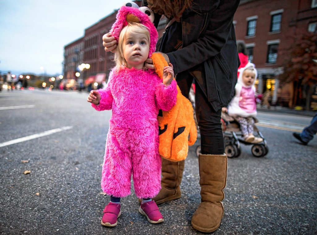 Allison Parkington, 2, gets her headress adjusted by her mom at the Halloween Howl on Main Street in Concord on Friday evening, October 25, 2019. GEOFF FORESTER