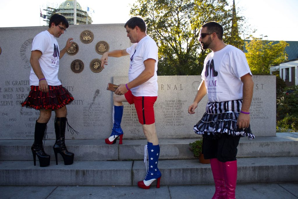 Adam Memmolo, right, Marc Racine, center, and Bob McCullen, left, all with the Grappone team for Walk A Mile In Her Shoes, arrange themselves for a cell phone photo on Wednesday, Oct. 5, 2016.