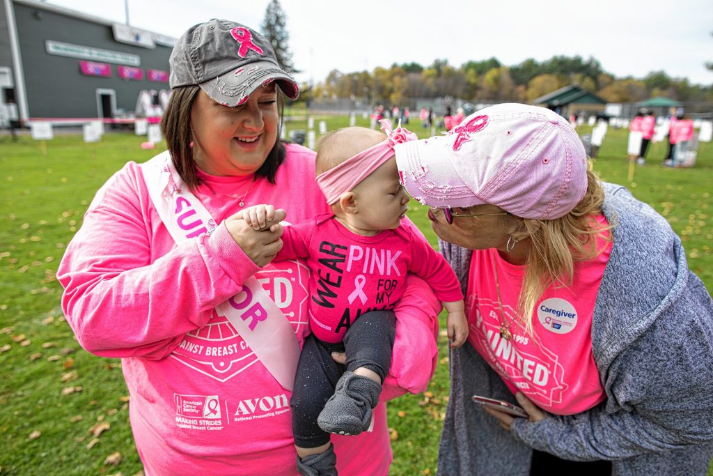 Lauren Allison holds her niece, Lucy Freese as she investigates the Making Strides balloons at the photo booth at Memorial Field in Concord before the walk on Sunday, October 20, 2019. The pair were walking for Lauren's sister. GEOFF FORESTER