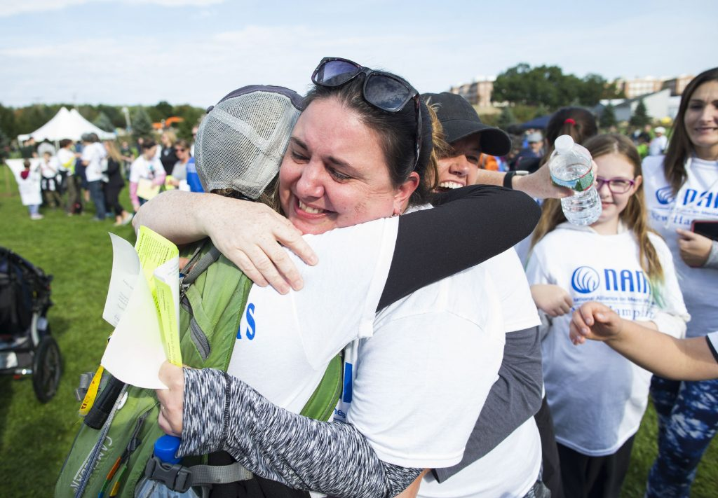 Heather Anderson of Hillsboro gets a hug after getting emotional after taking a group photo for Bonnie's Soul Sisters in memory of her sister Bonnie who died in 2001 before the NAMI Walk on Sunday, September 30, 2018. GEOFF FORESTER