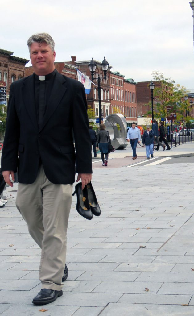 Rev. Jonathan Hopkins of the Concordia Lutheran Church heads to the Walk a Mile in Her Shoes 2018 event with heels in hand on Wednesday, October 3 2018. Caitlin Andrews