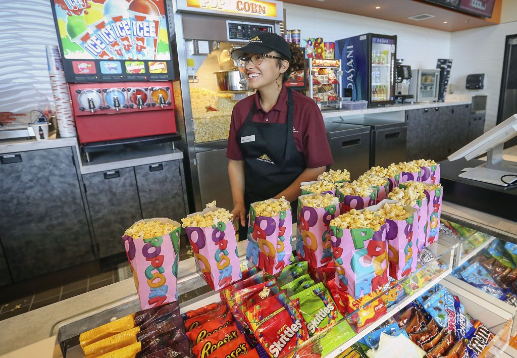 In this May 17, 2018 photo, McFarland High senior Victoria Sharp works at the food concession and is one of the high school students that acquired one of the coveted jobs at the Maya Cinemas Theater in Delano, Calif. For around a decade, the farm worker city of Delano, has lacked a movie theater. Residents from this largely Latino community had to travel nearly 40 miles to see the latest film a drive advocates say was rare since around a third of the population lives in poverty. This week, Moctesuma Esparza, a well-known Latino movie producer, opened his latest Maya Cinemas theater this month in the Central California city of 53,000 people as part of his ongoing effort to open movie theaters in poor, U.S. rural areas that lack basic entertainment options. (Henry A. Barrios/The Bakersfield Californian via AP)  Henry A. Barrios