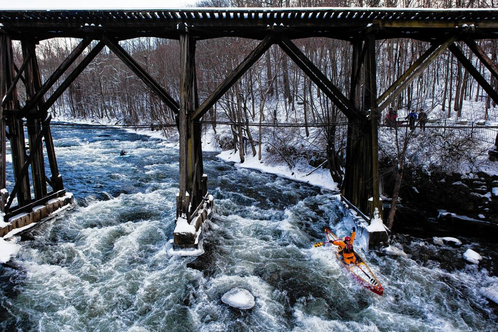Harry Wallace celebrates while passing underneath the railroad trestle across the Winnipesaukee River in Franklin during the annual First Day Kayak Run on Wednesday, January 1, 2014. Roughly 40 paddlers from the Merrimack Valley Paddlers and other New England outdoor associations battled class III and IV rapids while braving temperatures in the teens. (WILL PARSON / Monitor staff)