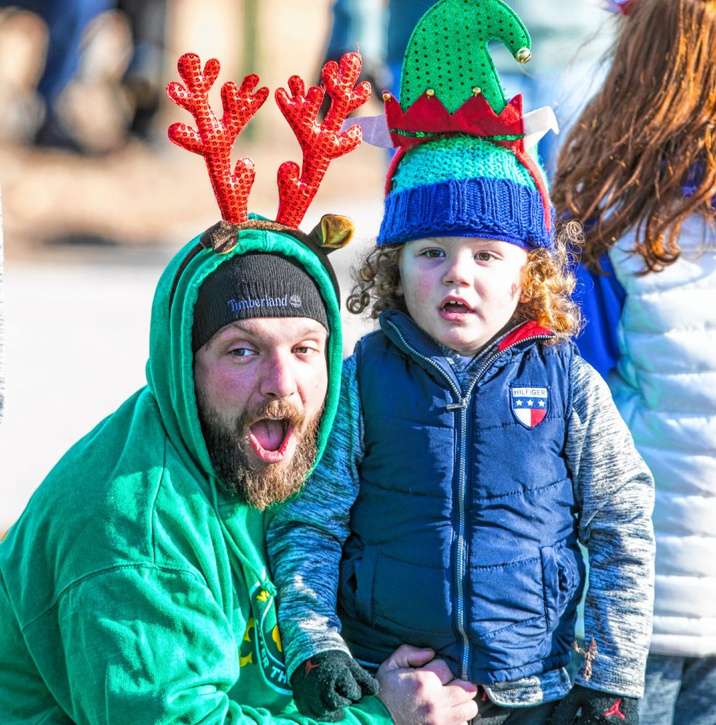 Brian McKeon and his son Kannon react to the Concord fire trucks as they sound off their sirens to start the 68th Annual Grange 322 Christmas Parade down Loudon Road on Saturday morning, November 23, 2019. GEOFF FORESTER