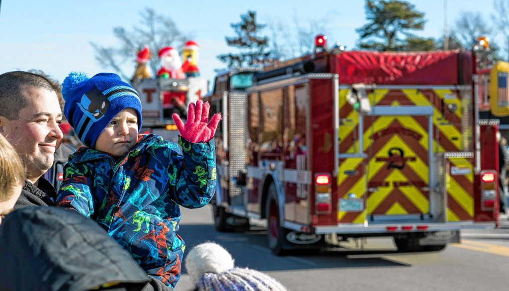 Cohen Trudell, 3, waves at the ambulances and fire trucks with his father Andrew at the 68th annual Grange 322 Concord Christmas parade down Loudon Road on Saturday morning, November 23, 2019. GEOFF FORESTER