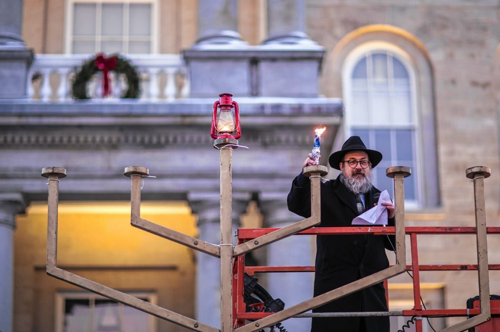 Rabbi Levi Krinsky of  Chabad Center for Jewish Living, New Hampshire holds up a lighting candle after the Menorah Lighting at the State House on Sunday evening, December 22, 2019. Hanukkah is an eight-day Jewish festival with the first day known as Chanukah, Festival of Lights, and Feast of Dedication.  GEOFF FORESTER