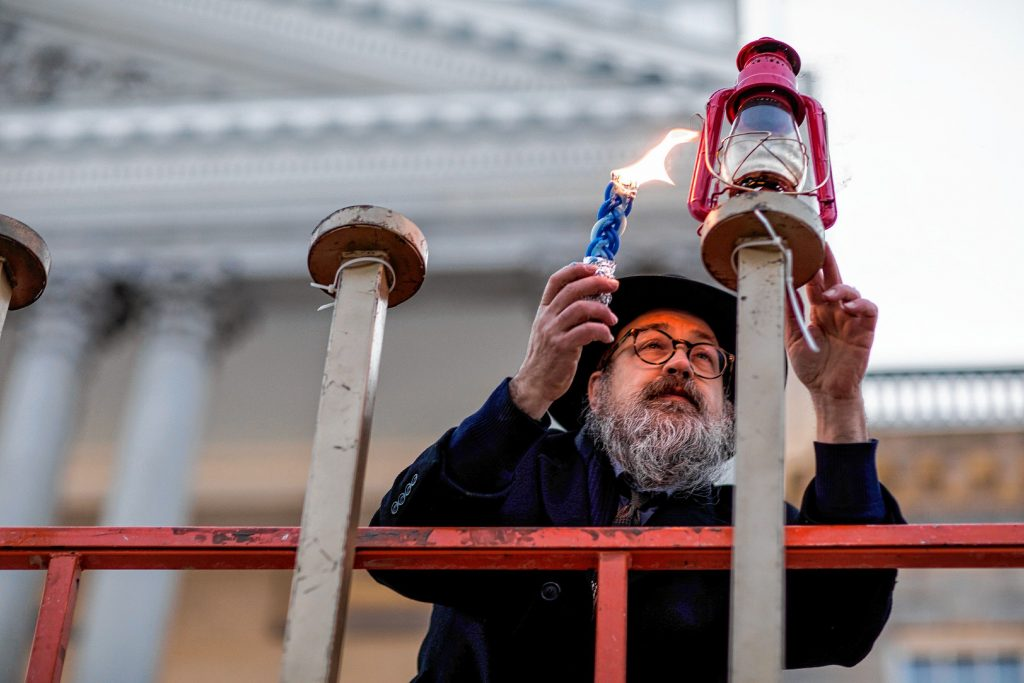 Rabbi Levi Krinsky of  Chabad Center for Jewish Living, New Hampshire holds up a lighting candle at the Menorah Lighting at the State House on Sunday evening, December 22, 2019. Hanukkah is an eight-day Jewish festival with the first day known as Chanukah, Festival of Lights, and Feast of Dedication.  GEOFF FORESTER