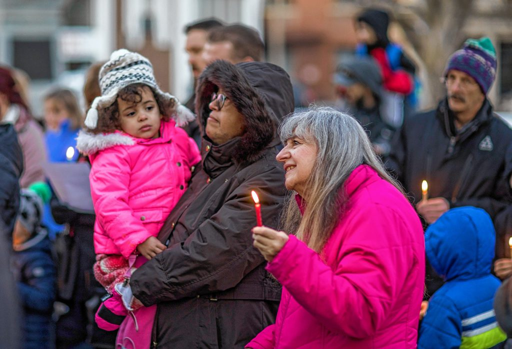 Gloria Fulmer of Londonderry holds a candle during the Menorah Lighting at the State House as her daughter Charlene Elliston and granddaughter Mariah Elliston, 3, look on at the ceremony on Sunday evening, December 22, 2019. Hanukkah is an eight-day Jewish festival with the first day known as Chanukah, Festival of Lights, and Feast of Dedication. GEOFF FORESTER