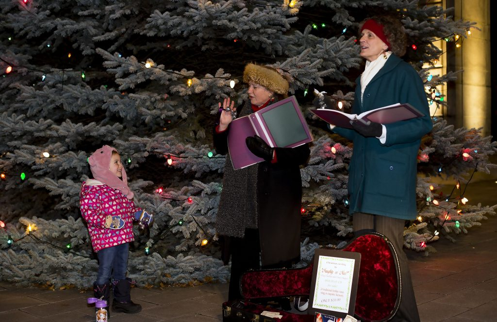 Peg Chaffee, right, and Cheryl Sagler—known as Naughty N Nice—get some help from Ava Pike, 4 as they sing at City Plaza during Midnight Merriment Friday night in downtown Concord. GEOFF FORESTER