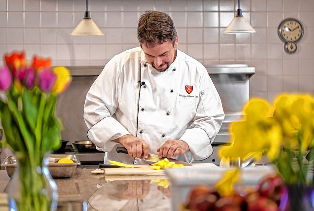 Bradley Labarre, rectory chef at St. Paul's School, demonstrates some of his skills on the job recently. Labarre will compete against two other Granite State chefs in the New Hampshire Food Bank Steel Chef Challenge in Manchester on March 11. Courtesy of Derek Thomson