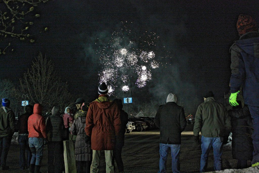 People watch the fireworks show over the baseball field at White Park during the 1883 Black Ice Pond Hockey Championship on Jan. 26, 2019.
