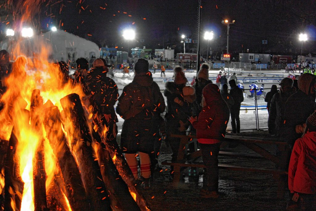 The massive bonfire was a very popular spot on this cold Saturday night of the 1883 Black Ice Pond Hockey Championship at White Park.