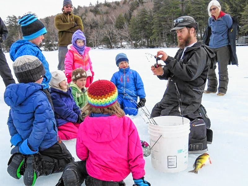 Squam Lake staff teach children the basics of ice fishing with a jig rod.