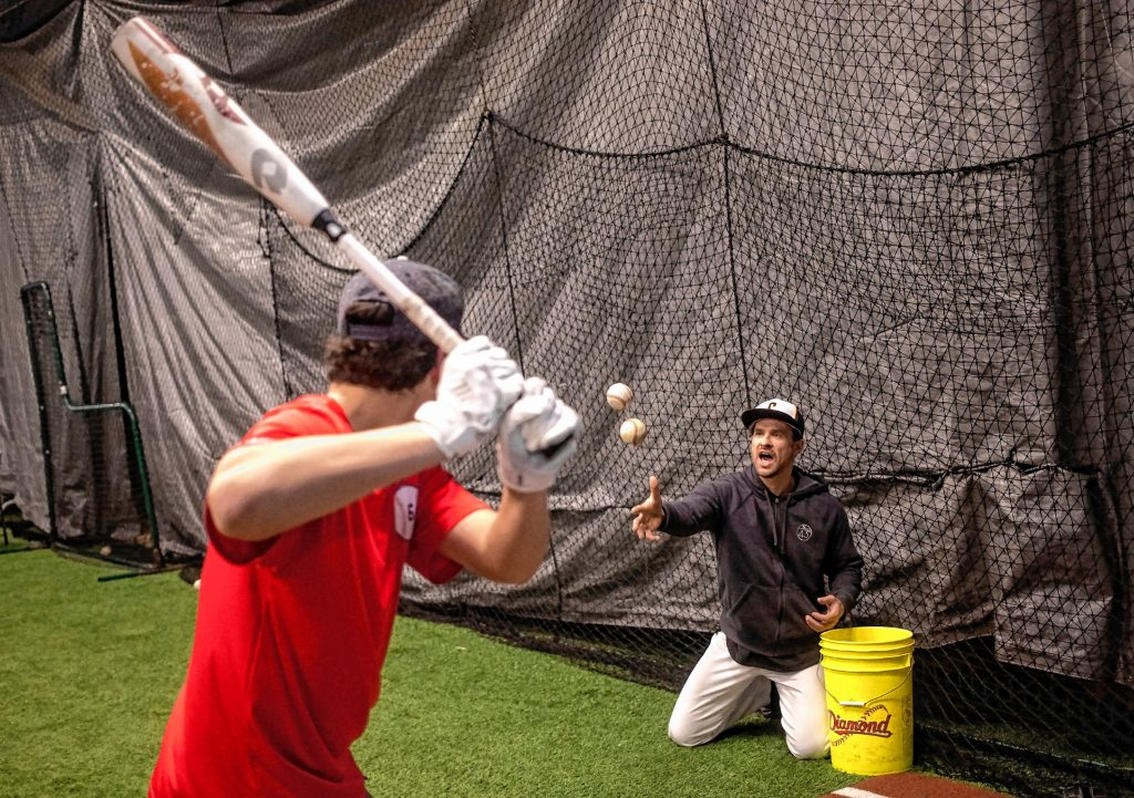 Former professional baseball player Matt Tupman yells out for a batting drill called High Low to Concord High School catcher Jarrad Willette at the Concord Sports Center off of exit 17 in Concord on Thursday evening, January 23, 2020.