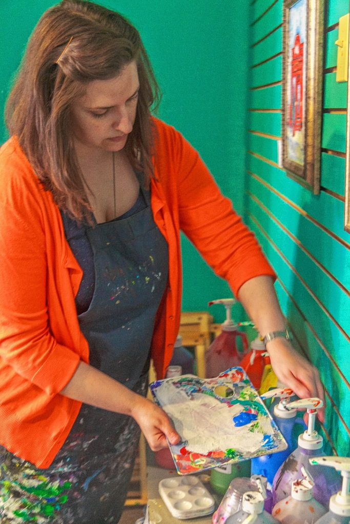 Christa, owner of The Place Studio and Gallery, pours some paint to get ready for a class. July 22, 2016 (JENNIFER MELI / Monitor Staff)