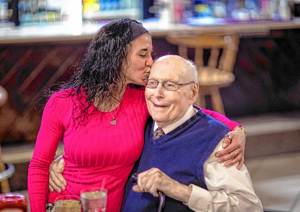 Kyme Locke places a kiss on the side of the head of World War II veteran Herb Kavash, 94, at the Post 21 in Concord on Thursday, January 9, 2020. GEOFF FORESTER