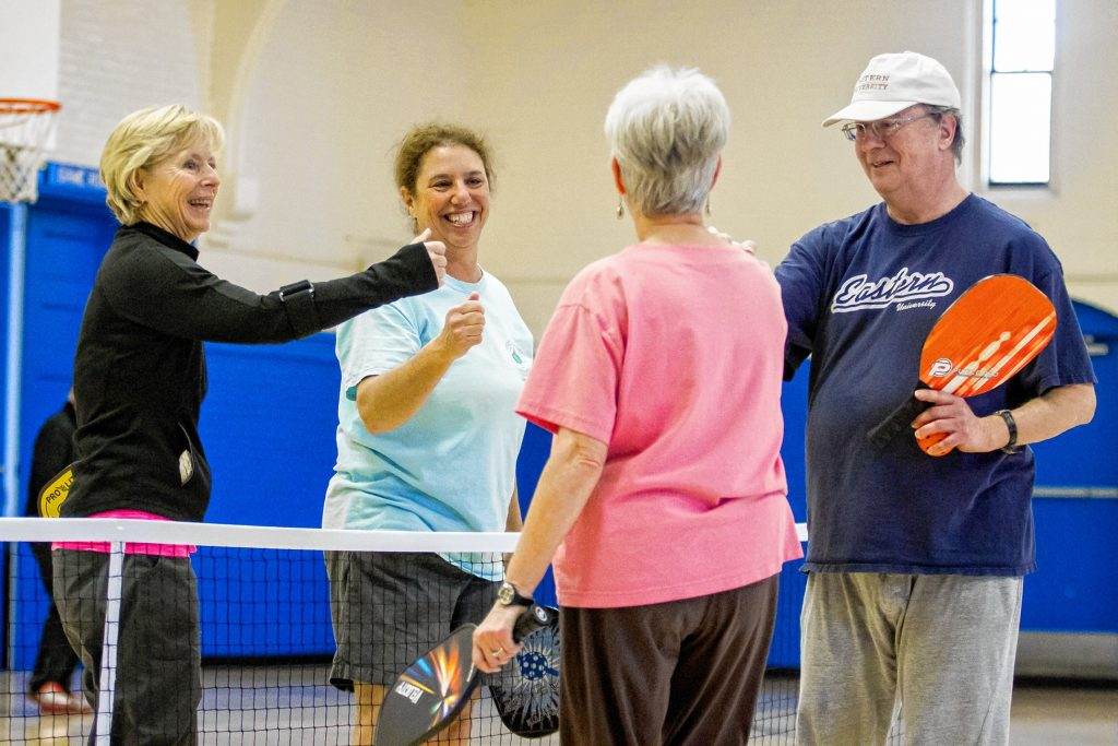 Celine Boucher (left to right), Deb Dickerson, Donna Roscoe and Brian Graf meet at the net to bump fists at the end of a game of pickleball at the Green Street Community Center in Concord on Friday, Jan. 26, 2018. ELIZABETH FRANTZ