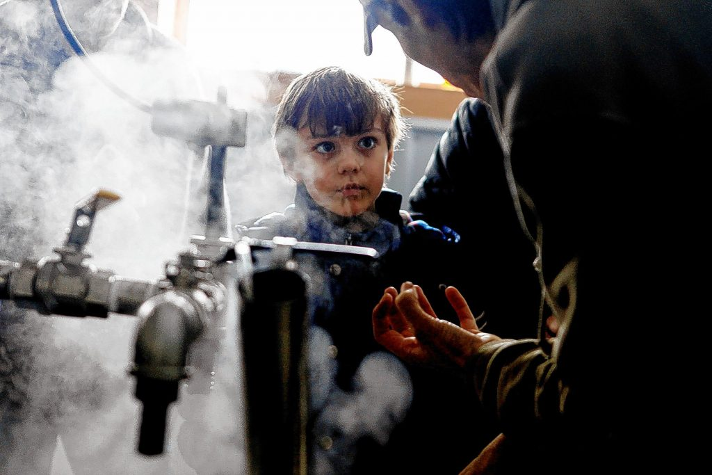 James Russell of Concord, 8, listens to Stefan Lillios explain how to make maple syrup in the boiling room at Maple Ridge Sugar House in Loudon on Saturday, March 22, 2014.