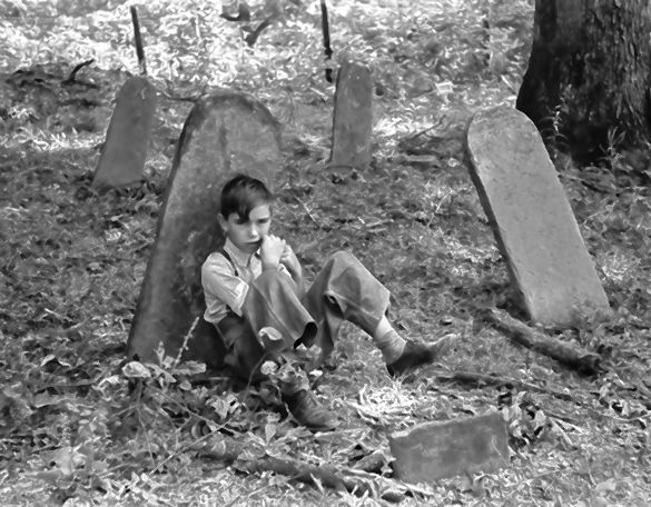 A boy sits on a family member's grave in 1940.