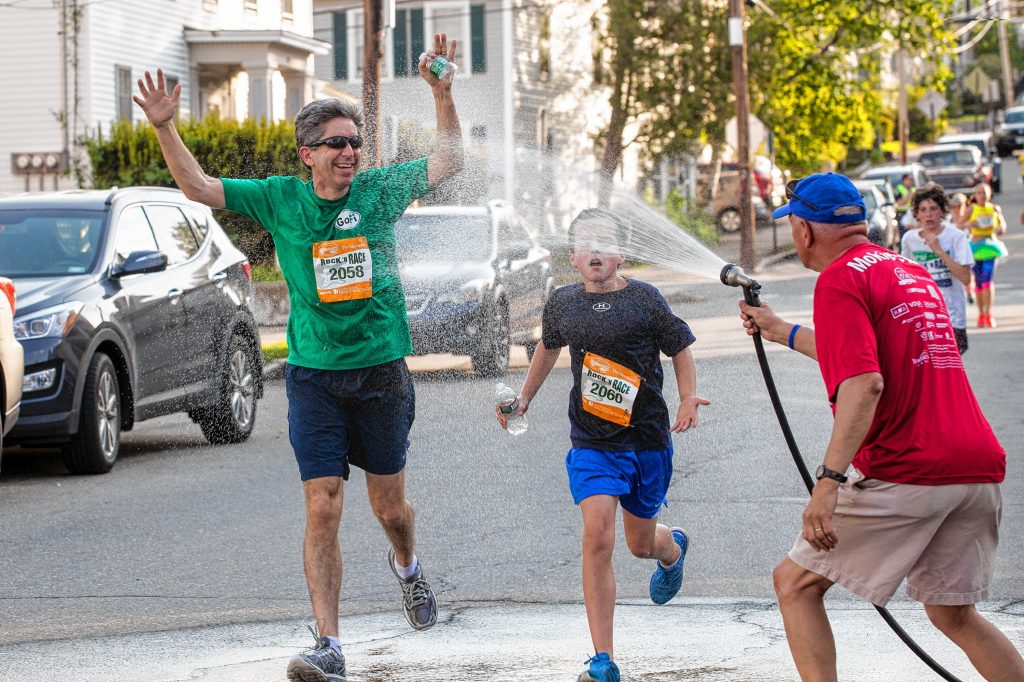 Niall (left) and Rory Campbell welcome the sprayed water offered by Roger Jobin (right) at the Northwestern Mutual station during Rock 'N Race 5K in downtown Concord on Thursday, May 18, 2017. ELIZABETH FRANTZ