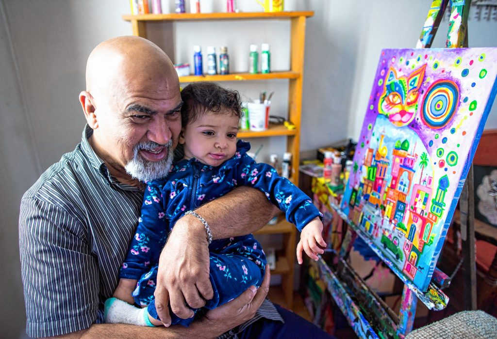 Saad Hindal with his granddaughter Hawrra in his upstairs studio in his living room on Sept. 21, 2018. He showed his work at the Multicultural Festival at the State House in 2018. Geoff Forester