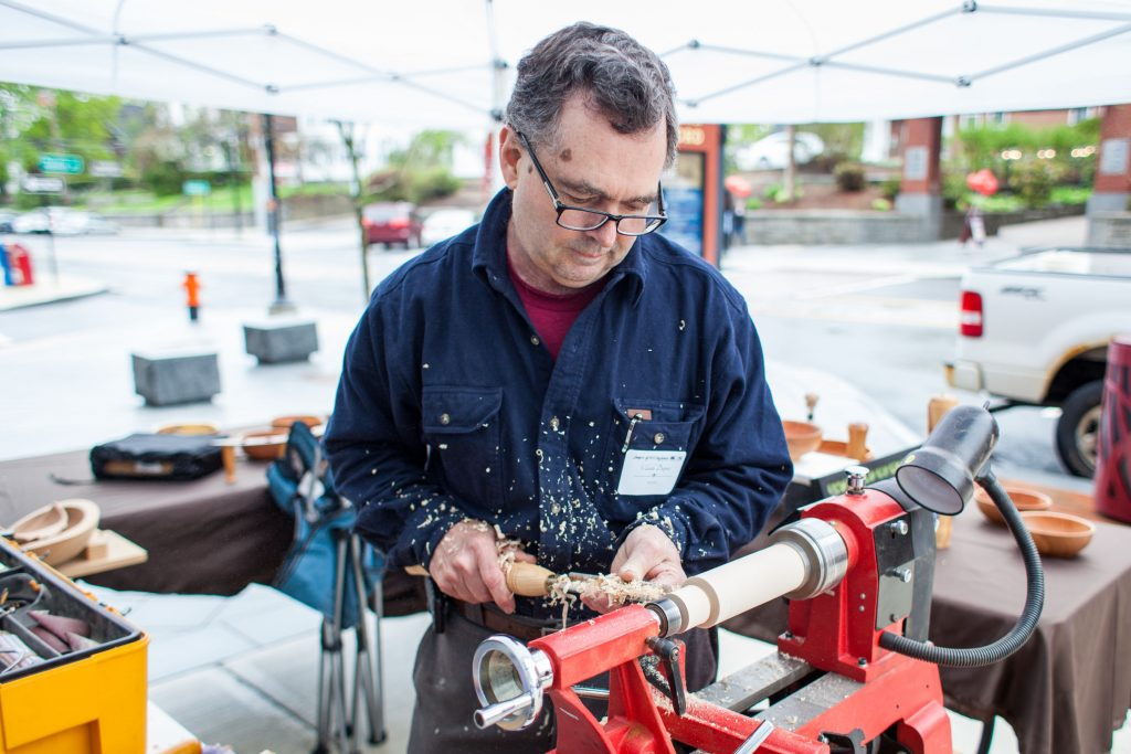 Claude Dupuis of Canterbury carves a wooden top using a motor-driven lathe outside the League of New Hampshire Craftsmen Headquarters in downtown Concord during Capital Arts Fest on Saturday, May 6, 2017. (ELIZABETH FRANTZ / Monitor staff) Elizabeth Frantz