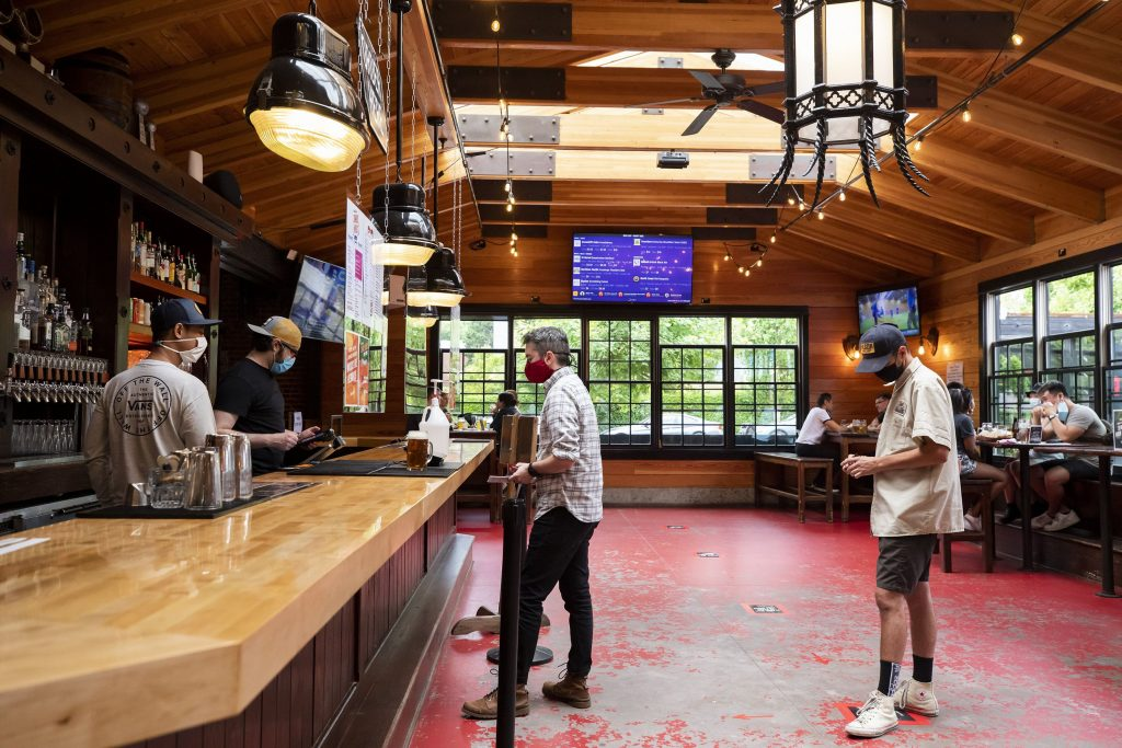 Brandon Owen and Charles McLean, right, line up to order at the bar at Rhein Haus Seattle on July 16, 2020. Both Owen, a server, and McLean, a sous chef, are not working at their respective local restaurants right now due to the pandemic. Safety measurements for COVID-19 seen at the bar include mandatory masks, industrial fans to increase airflow, social distancing while ordering and at tables, plexiglass dividers shielding bartenders, new contactless point-of-sale devices, and constant cleaning and disinfecting. (Bettina Hansen/Seattle Times/TNS) Bettina Hansen