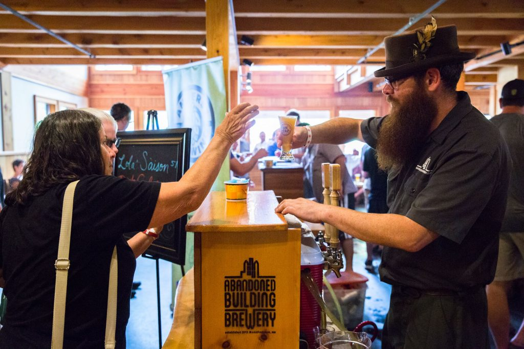 Paul Nichols, of Abandoned Building brewery in Easthampton, serves a beer to an attendee of Franklin County Beer Fest at Berkshire East in Charlemont Saturday, July 22, 2017. Recorder Staff/Matt Burkhartt