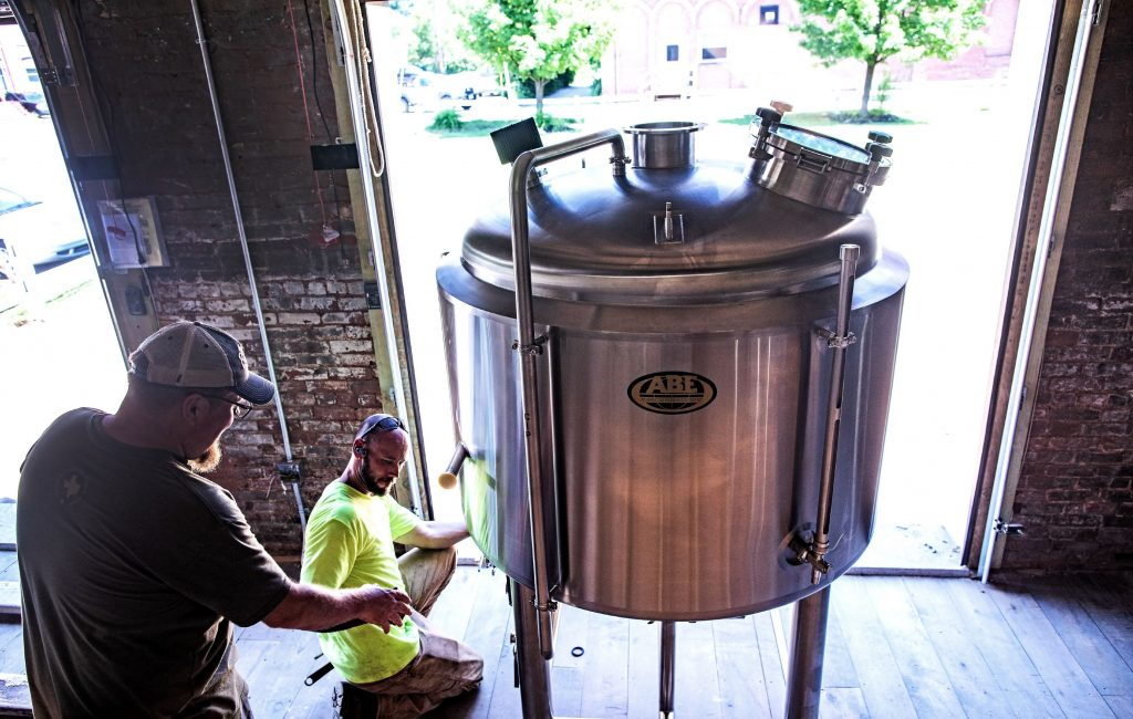 Damon Lewis (left), co-owner of the new Vulgar Brewery in downtown Franklin, helps Russell Belmer of Shaughnessy Rigging of Deerfield move a seven barrel boil kettle into the new brewery on Monday, July 1, 2019. The brewery is one of the places in Franklin getting financing from Franklin Savings Bank. GEOFF FORESTER