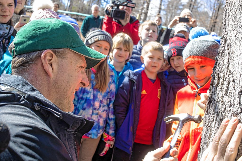 New Hampshire Governor Chris Sununu puts in a tap at Mapletree Farm on Oak Hill Rd in Concord on March 5, 2020 at the annual N.H. Maple Tree Tap as school children from the Shaker Road School in Concord watch.