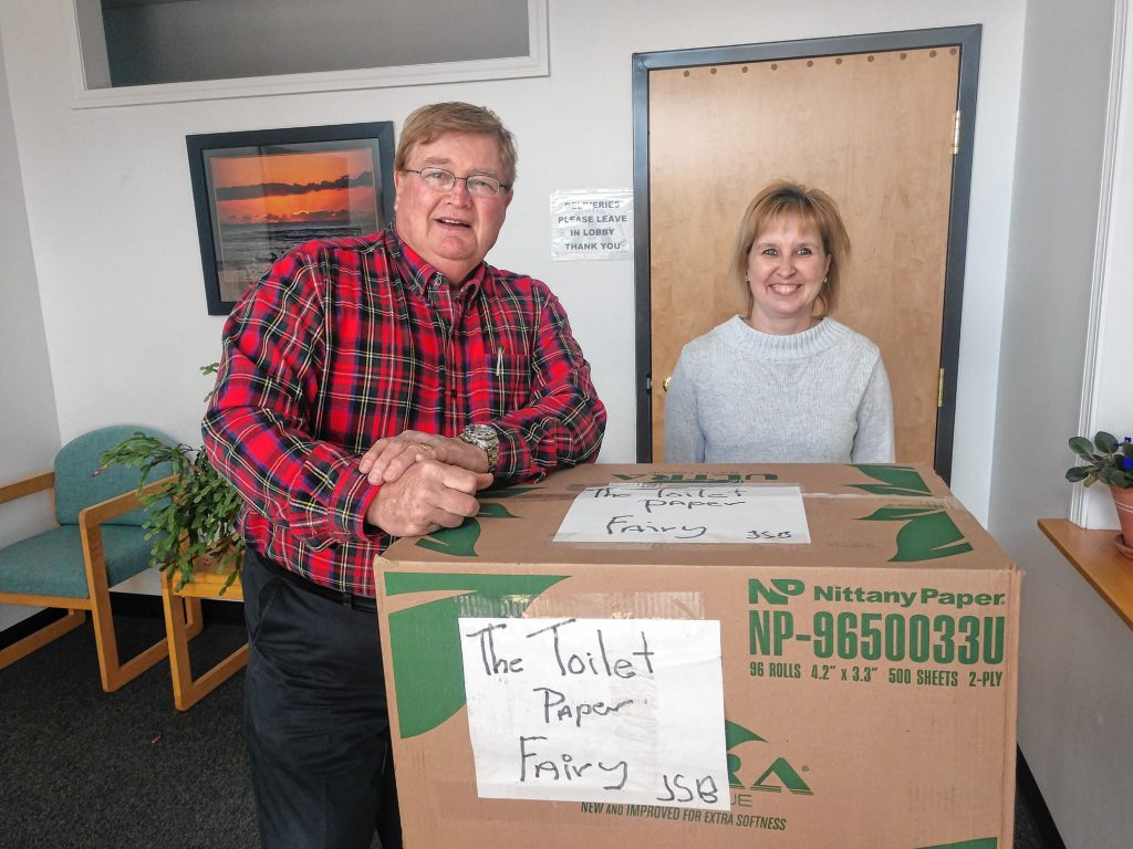 John Ball donates a supply of toilet paper to Michelle Beaudin, the program coordinator for Meals on Wheels in Merrimack and Belknap Counties.
