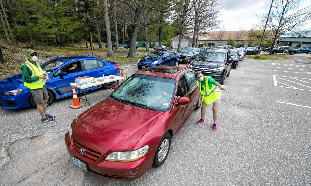 Hopkinton School board candidate—and voter check-in worker—Dulcie Lipoma directs cars where to drive to cast their votes at Hopkinton High School on Saturday morning, May 16, 2020. The line of cars to vote went all the way back to the center of Contoocook.