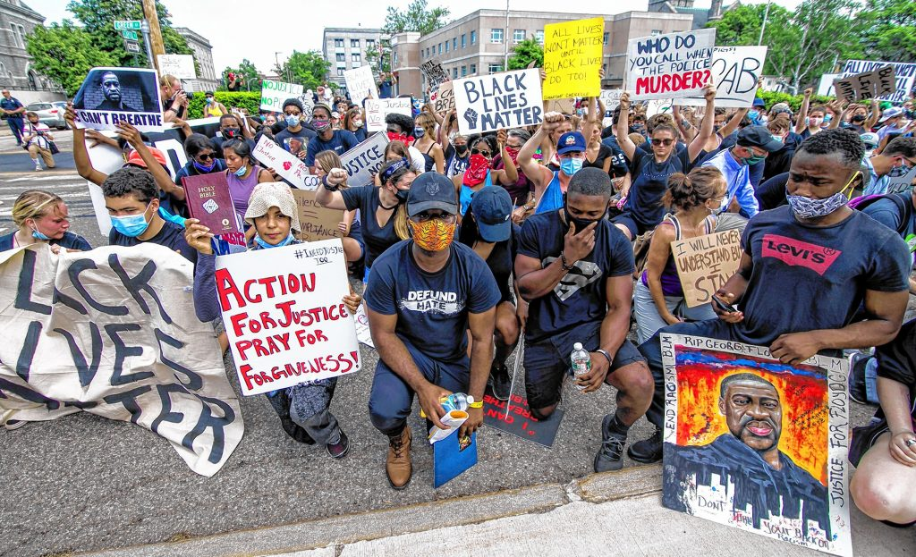 The Black Lives Matter demonstrators take a knee in front of the Concord Police station on their way to the State House during their rally on Saturday afternoon, June 6, 2020.