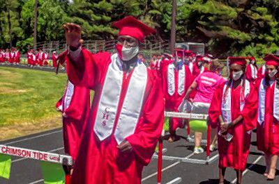 Concord High School graduate Hamza Abdulrahman waves to a teacher as he lines up for the 2020 graduation for the Commons B at Memorial Field on Saturday, June 13,2020.