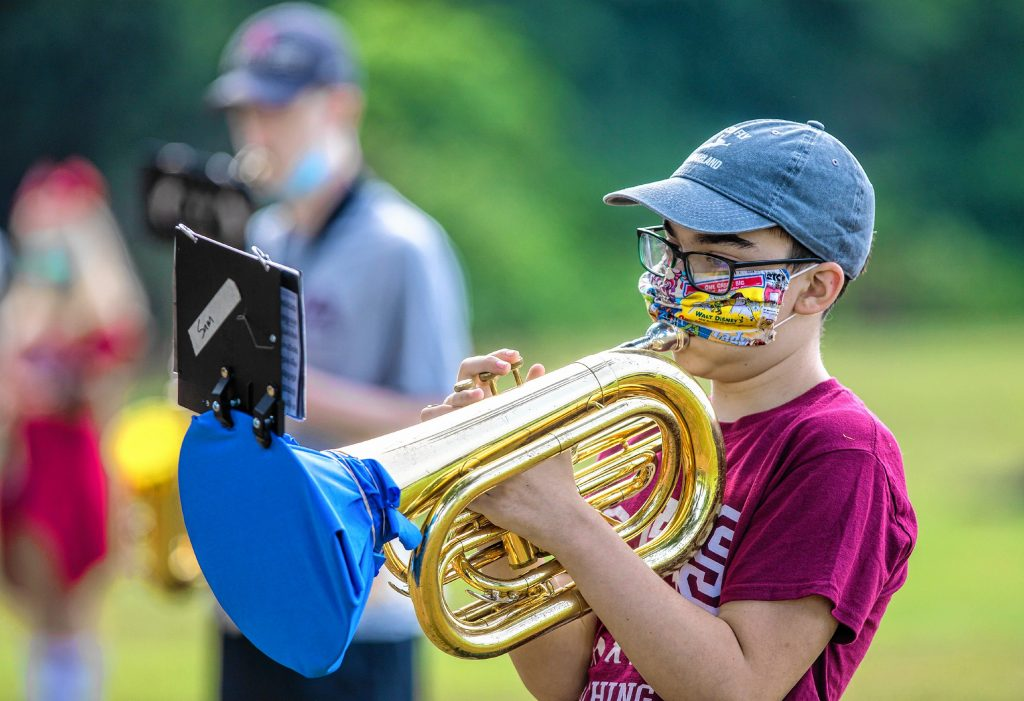 Concord High School marching band member Sam Kraus covers his Baritone horn during morning practice at Memorial Field on Tuesday, August 25, 2020.