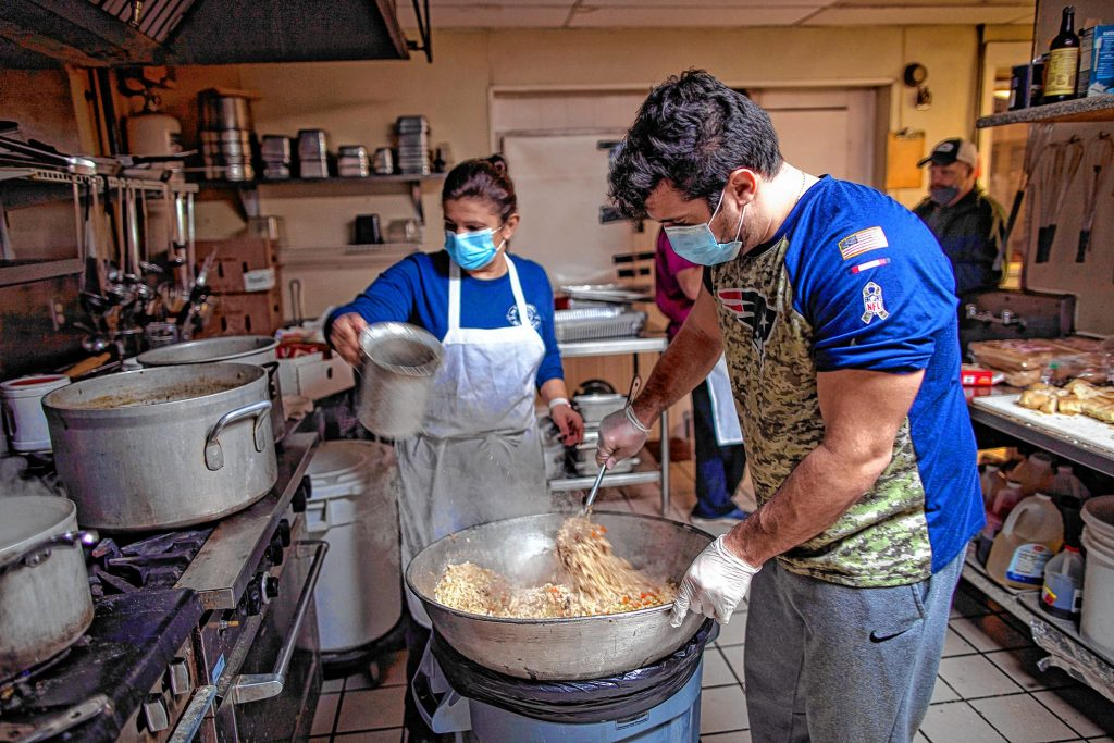 Windmill owner Kosmas Smirnioudis' brother Michael stirs the stuffing as he is mother Sofia pours in water to mix it as they have started preparing meals for the annual Thanksgiving dinner. The restaurant's holiday tradition will continue but now with takeout and delivery for next Thursday.