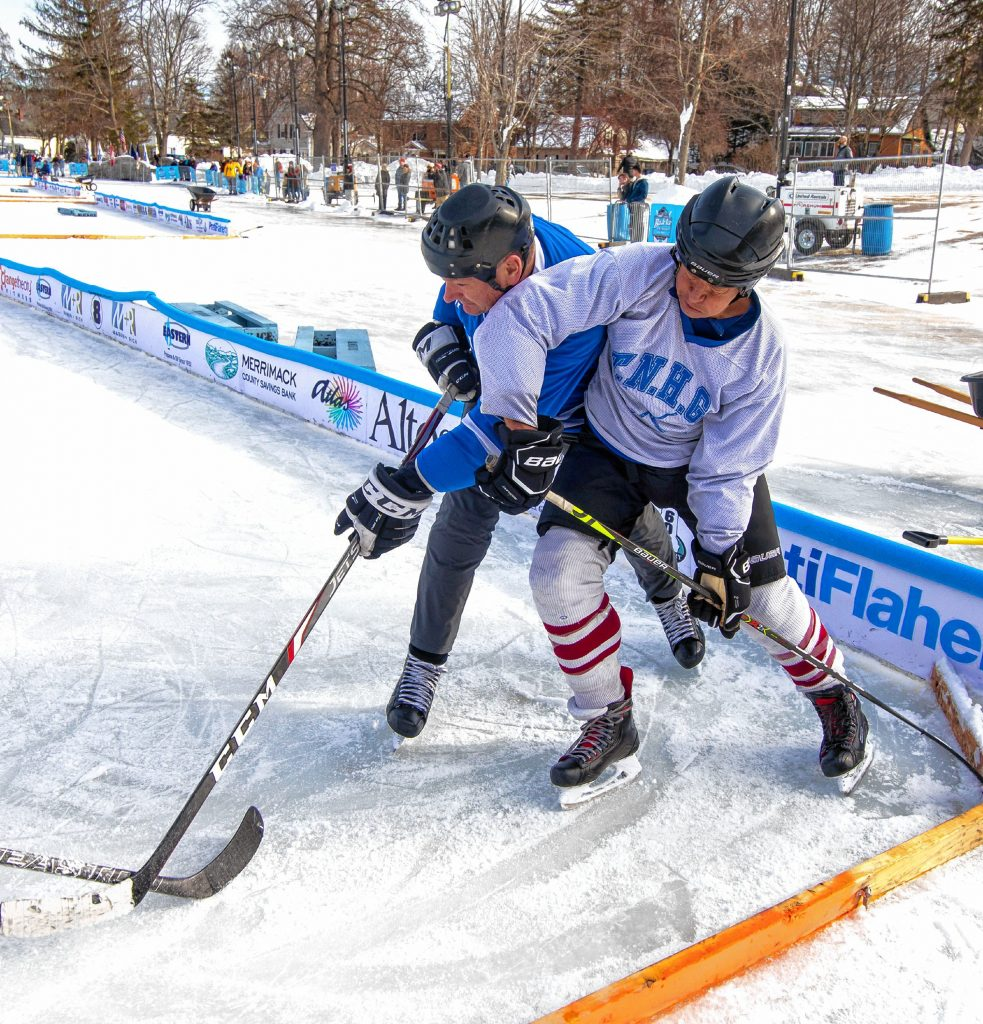 Team captain Tim Grenier of the West Pond Hockey Club of Essex, Massachusetts (right) battles a Pickups team player during a morning game of the opening of the 10th annual Black Ice Pond Hockey Championships at White Park on Friday, January 24, 2020. Grenier said he was looking forward to beating the Pickups this year after losing to them last year. The game ended in a tie. Geoff Forester