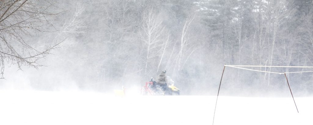 A worker at Beaver Meadow golf course in Concord uses a snowmobile to drag a grater to form the cross country ski trails on the course as wind and blowing snow blast the open area on Monday, January 21, 2019. GEOFF FORESTER