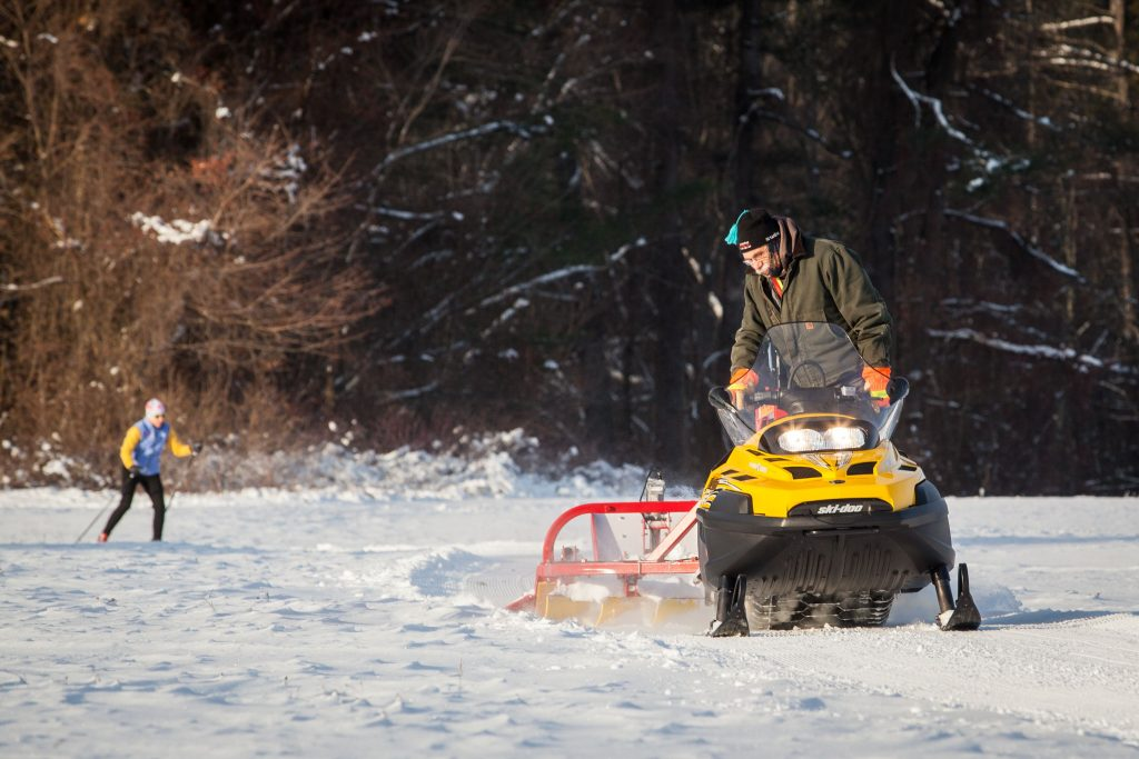 Long-time volunteer Frank Muller passes over the trails at White Farm in Concord with a snow groomer as his wife, Kate Fox skis behind him on Saturday morning, Dec. 31, 2016. (ELIZABETH FRANTZ / Monitor staff) Elizabeth Frantz