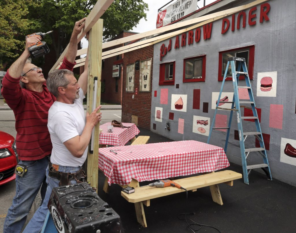 Carpenters Tom Percoco, left, and Dan Mercier build an outdoor dining area at the Red Arrow Diner in Manchester, N.H., Monday, May 18, 2020. The diner, which closed their inside dining area in March due to business restrictions created by the COVID-19 virus outbreak, expects to open their outdoor area for customers later in the day once construction is complete. Restaurants across New Hampshire reopened to outdoor table service on Monday. (AP Photo/Charles Krupa)  Charles Krupa