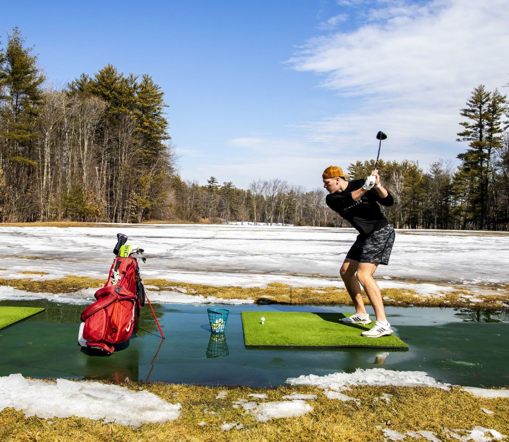 """Camden Gagnon of Goffstown uses his iron for the first time this season at the Beaver Meadow driving range which just opened up for the season on Thursday, March 11, 2021. Asked why he traveled all the way from Goffstown, Gagnon replied, ''it was the only place open."""" GEOFF FORESTER"""