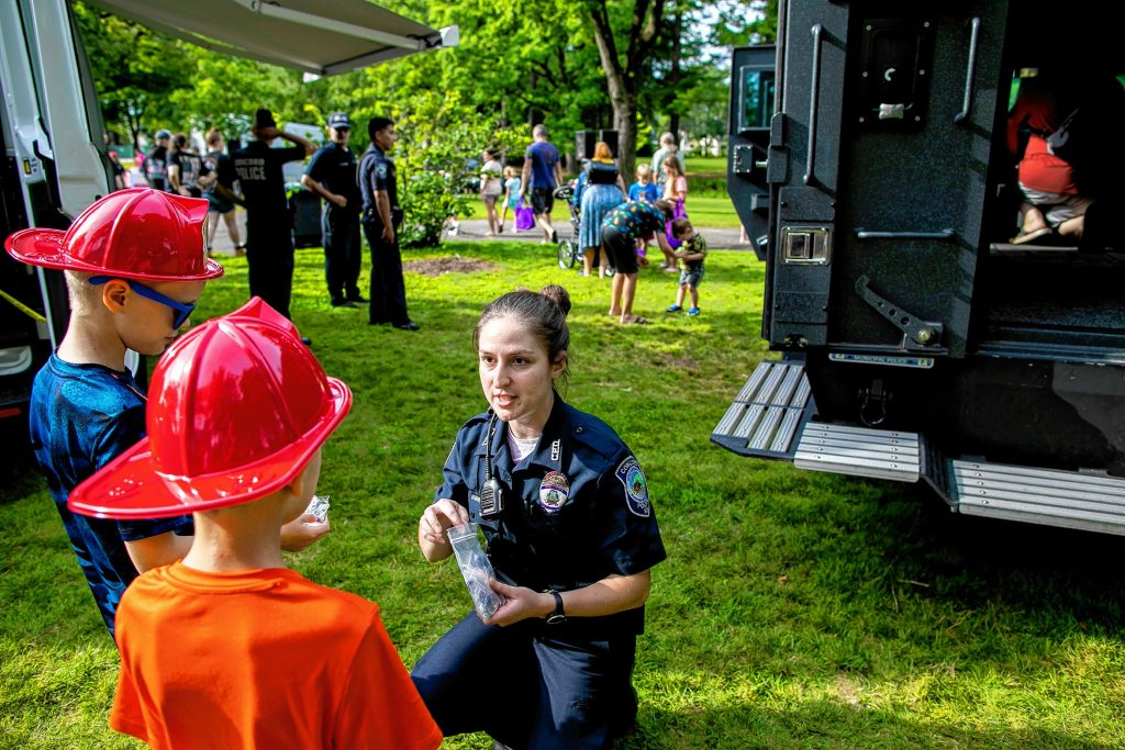 New Concord police officer Laura Dzgoeva hands out gifts to kids at the National Night Out at Rollins Park on Tuesday, August 3, 2021. Dzgoeva speaks both Russian and German and joined the force this year. GEOFF FORESTER