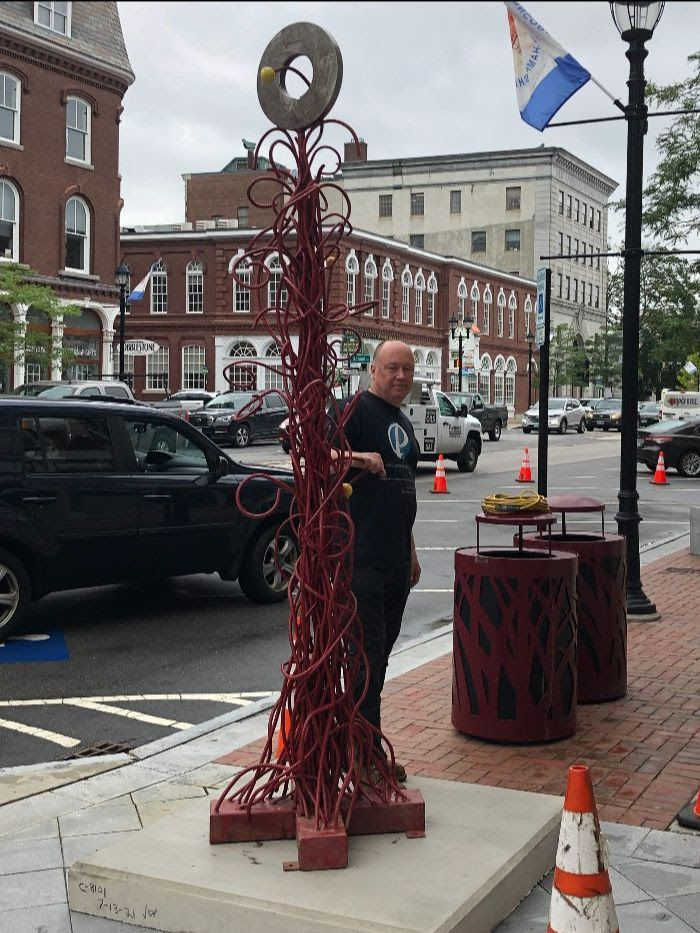 Chris Plaisted stands with one of his  two sculptures recently installed downtown.